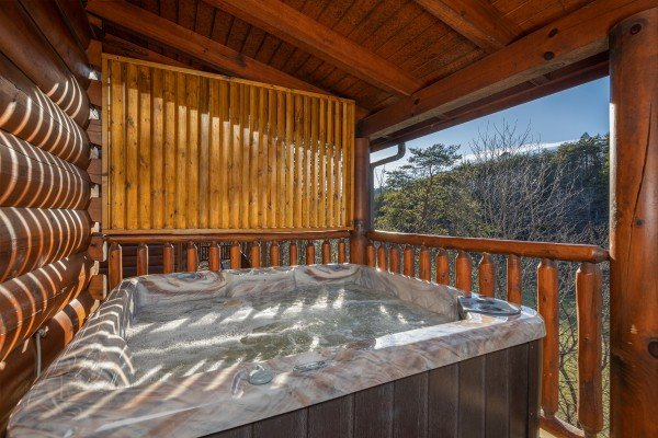 Hot tub on a covered deck at Southern Comfort Memories, a 2 bedroom cabin rental located in Pigeon Forge