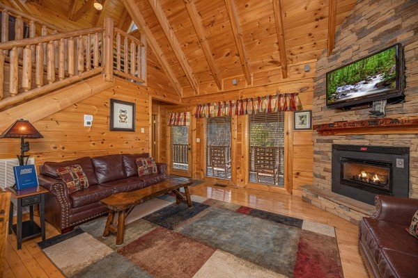 Living room with fireplace and TV at Southern Comfort Memories, a 2 bedroom cabin rental located in Pigeon Forge
