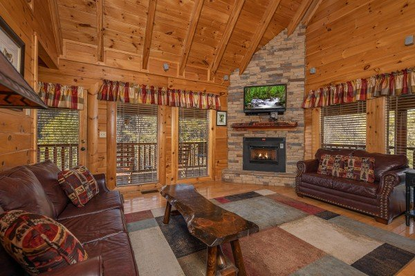 Living room with fireplace, TV, and leather seating at Southern Comfort Memories, a 2 bedroom cabin rental located in Pigeon Forge