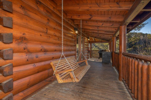 Porch swing on a covered deck at Southern Comfort Memories, a 2 bedroom cabin rental located in Pigeon Forge
