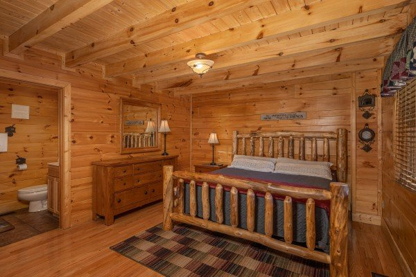 King bed, dresser, and en suite bathroom at Southern Comfort Memories, a 2 bedroom cabin rental located in Pigeon Forge