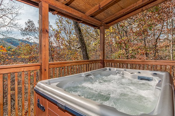 Hot tub on a covered porch at Shy Bear, a 2 bedroom cabin rental located in Pigeon Forge