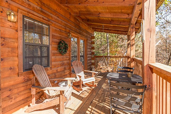 Porch with bistro set and Adirondack chairs at Shy Bear, a 2 bedroom cabin rental located in Pigeon Forge