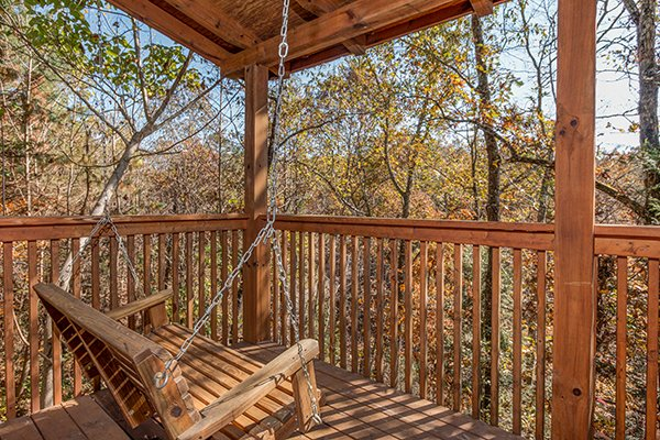 Porch swing facing the trees at Shy Bear, a 2 bedroom cabin rental located in Pigeon Forge