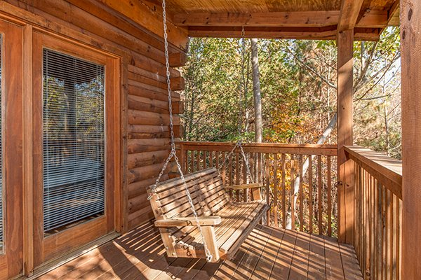 Swing on a covered deck at Shy Bear, a 2 bedroom cabin rental located in Pigeon Forge