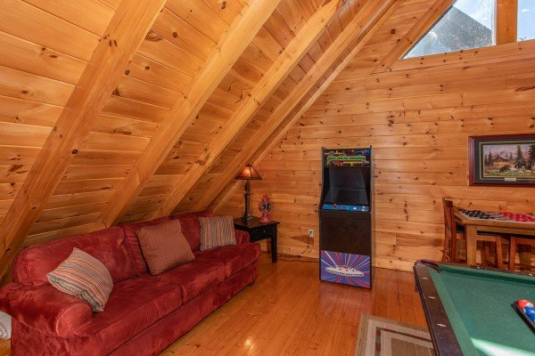 Game room sofa and arcade game in the loft at Bears Eye View, a 2-bedroom cabin rental located in Pigeon Forge