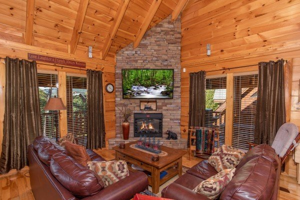 Living room stone fireplace and television at Bears Eye View, a 2-bedroom cabin rental located in Pigeon Forge