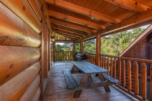 Picnic table on a covered deck at Bears Eye View, a 2-bedroom cabin rental located in Pigeon Forge