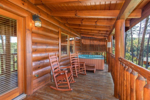 Rocking chairs and hot tub with a privacy fence on a covered deck at Bears Eye View, a 2-bedroom cabin rental located in Pigeon Forge