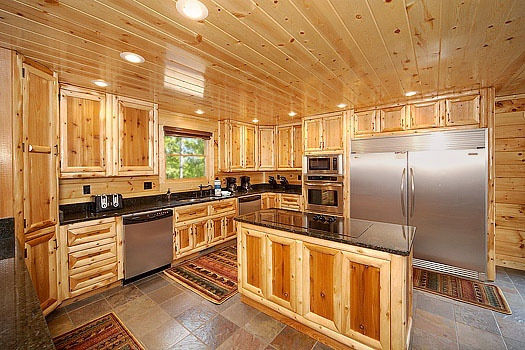 large kitchen with over sized stainless appliances at incredible! a 6 bedroom cabin rental located in gatlinburg