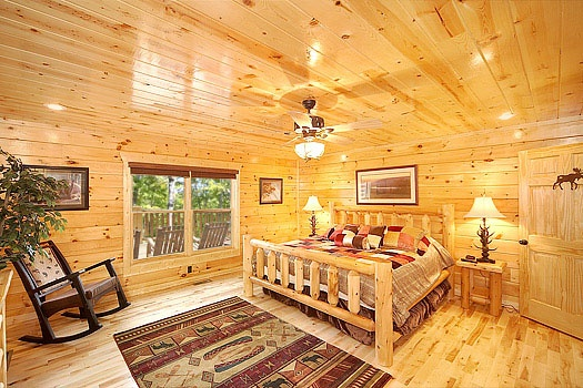 king sized log bed in the main level bedroom at incredible! a 6 bedroom cabin rental located in gatlinburg
