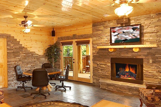 poker table next to fireplace in the second living room at incredible! a 6 bedroom cabin rental located in gatlinburg