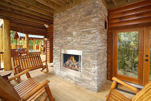 rockers around an outdoor fireplace at incredible! a 6 bedroom cabin rental located in gatlinburg