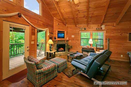 living room with stone fireplace at i do a 1 bedroom cabin rental located in pigeon forge