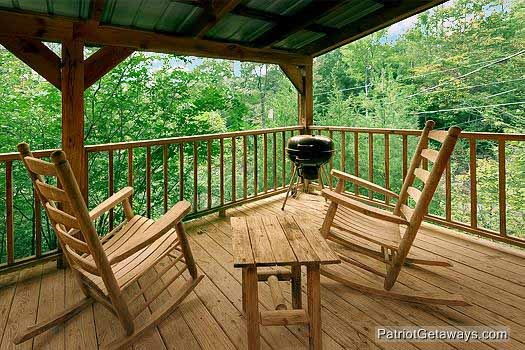 rocking chairs and charcoal grill on deck at i do a 1 bedroom cabin rental located in pigeon forge