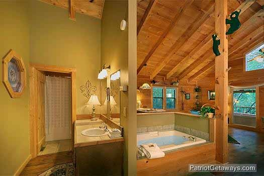 vanity adjacent to jacuzzi tub at i do a 1 bedroom cabin rental located in pigeon forge