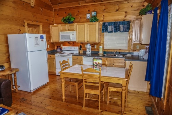 kitchen and dining area at just you and me baby a 1 bedroom cabin rental located in gatlinburg