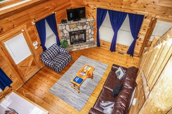 Living room with stone fireplace at Just You and Me Baby, a 1 bedroom cabin rental located in Gatlinburg