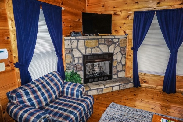 Stone fireplace in living room at Just You and Me Baby, a 1 bedroom cabin rental located in Gatlinburg