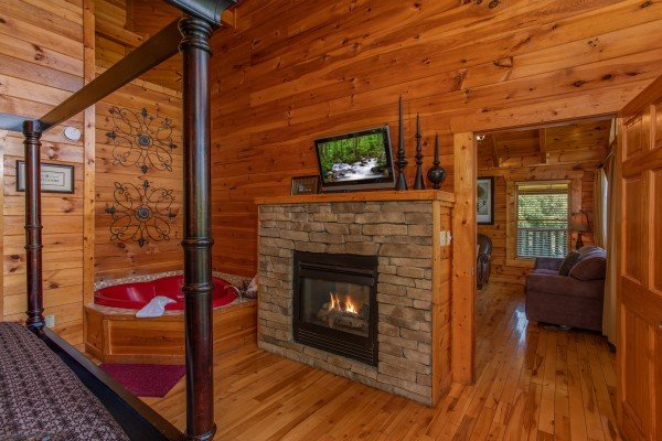 Fireplace and tv in the bedroom next to the jacuzzi at Majestic Sunrise, a 1 bedroom cabin rental located in Pigeon Forge