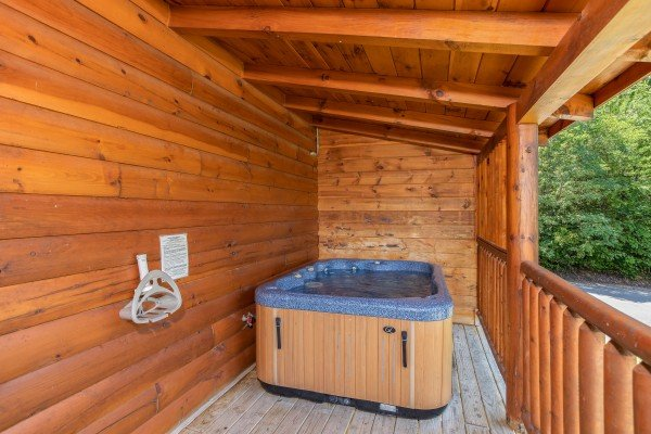 Hot tub on a covered deck at Majestic Sunrise, a 1 bedroom cabin rental located in Pigeon Forge