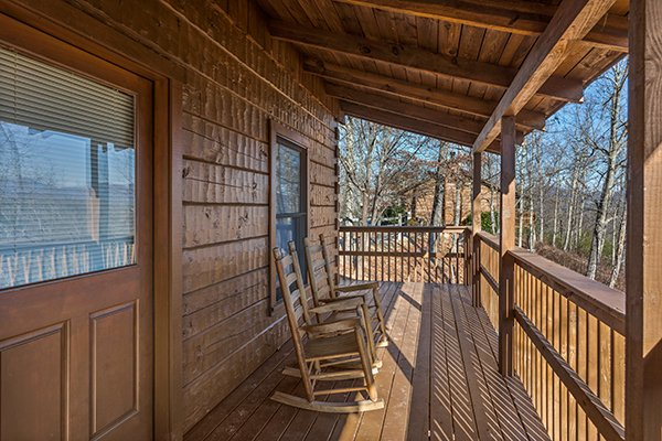 Rocking chairs on a covered deck at Mountain Magic, a 1 bedroom cabin rental located in Pigeon Forge