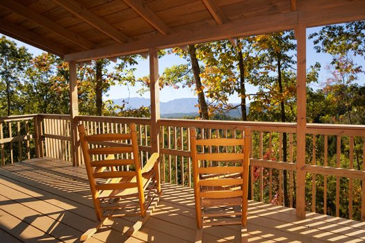 Deck with rocking chairs and view of the Smoky Mountains at Mountain Magic, a 1 bedroom cabin rental located in Pigeon Forge