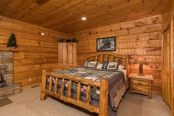 Bedroom with a king log bed at Mountain Magic, a 1 bedroom cabin rental located in Pigeon Forge