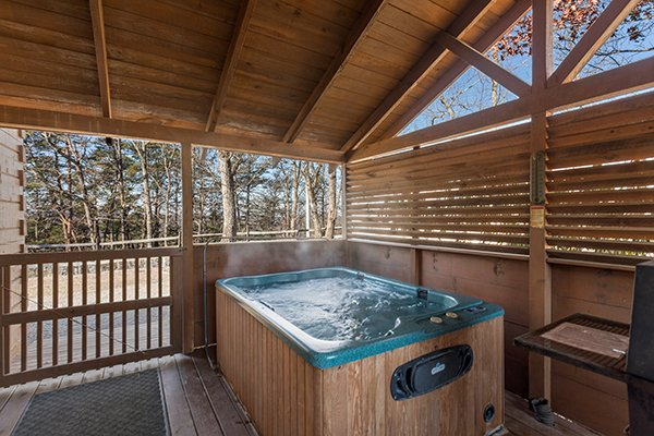 Hot tub on a covered deck with privacy fence at Mountain Magic, a 1 bedroom cabin rental located in Pigeon Forge