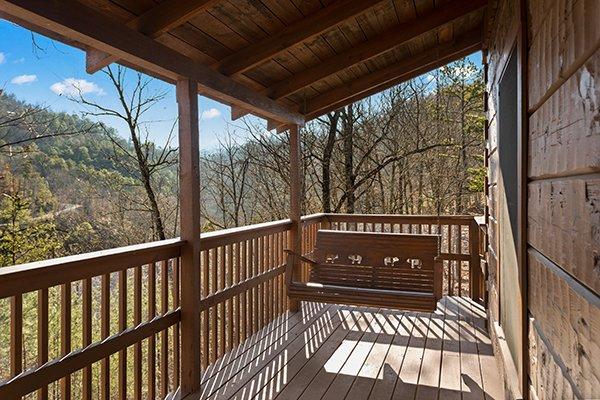Swing on a porch swing on a covered deck at Mountain Magic, a 1 bedroom cabin rental located in Pigeon Forge