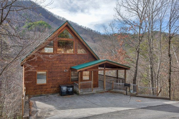 Exterior view of the cabin and flat paved parking pad at Alone Time, a 1 bedroom cabin rental located in Pigeon Forge