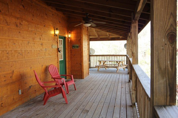 Adirondack chairs and picnic table on the covered deck at Alone Time, a 1 bedroom cabin rental located in Pigeon Forge