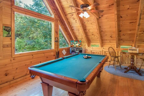 Loft with large picture window pool table and television at Alone Time, a 1 bedroom cabin rental located in Pigeon Forge