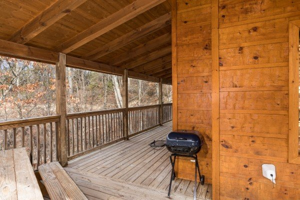 Charcoal grill and picnic table on covered deck at Alone Time, a 1 bedroom cabin rental located in Pigeon Forge