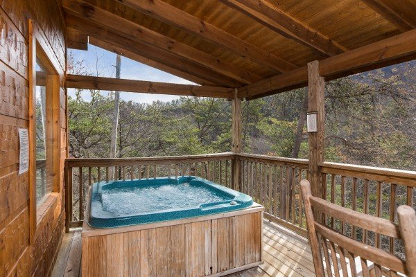 Hot tub on a covered deck with mountain views at Alone Time, a 1 bedroom cabin rental located in Pigeon Forge