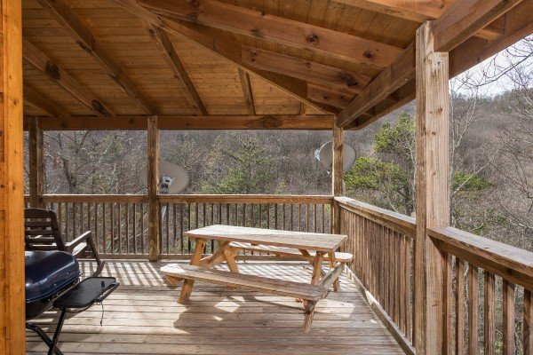 Picnic table on a covered deck at Alone Time, a 1 bedroom cabin rental located in Pigeon Forge
