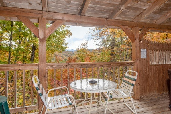 Covered deck with dining table for two at Love Me Tender, a 1 bedroom cabin rental located in Pigeon Forge
