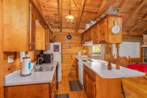Galley style kitchen with white appliances Love Me Tender, a 1 bedroom cabin rental located in Pigeon Forge