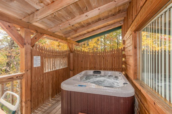 Hot tub on a covered deck with privacy fence at Love Me Tender, a 1 bedroom cabin rental located in Pigeon Forge