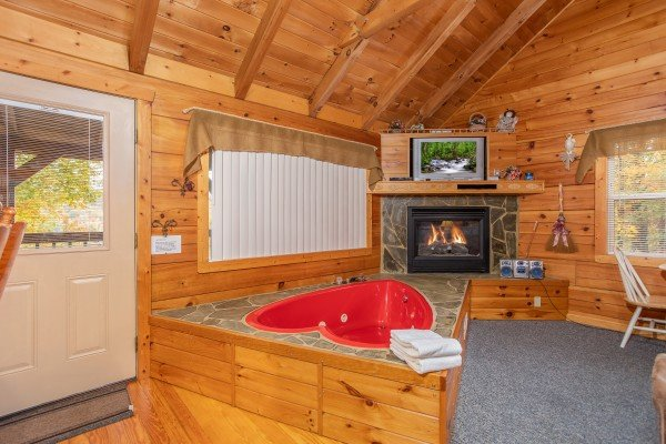 Heart shaped jacuzzi tub in front of a fireplace and television at Love Me Tender, a 1 bedroom cabin rental located in Pigeon Forge