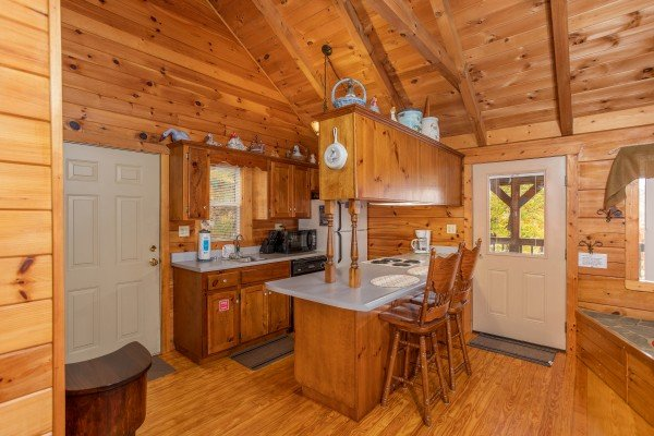 Kitchen and dining space for two at the breakfast bar at Love Me Tender, a 1 bedroom cabin rental located in Pigeon Forge