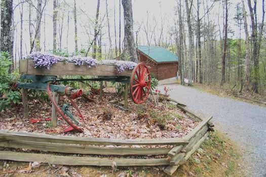 Old wagon in landscape at Love Me Tender, a 1 bedroom cabin rental located in Pigeon Forge