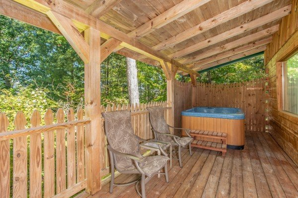 Hot tub and two chairs on a covered deck at Forever Yours, a 1-bedroom cabin rental located in Pigeon Forge
