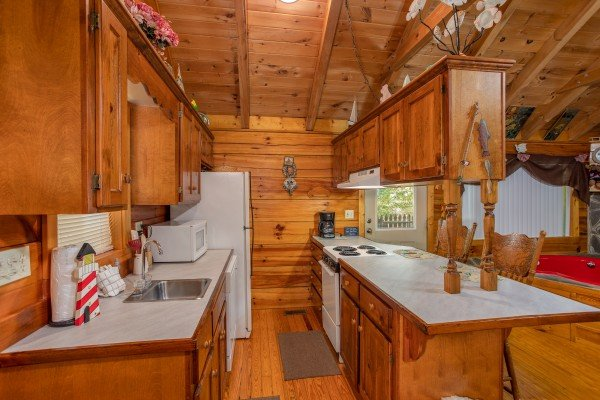 Galley style kitchen with white appliances at Forever Yours, a 1-bedroom cabin rental located in Pigeon Forge