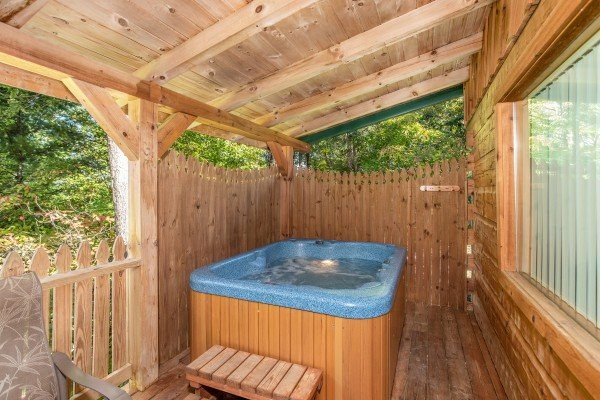 Hot tub with privacy fence on a covered deck at Forever Yours, a 1-bedroom cabin rental located in Pigeon Forge