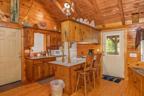 Kitchen with white appliances and counter top seating for two at at Forever Yours, a 1-bedroom cabin rental located in Pigeon Forge