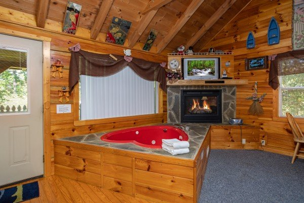 Studio living room with heart-shaped jacuzzi tub, fireplace, and TV at Forever Yours, a 1-bedroom cabin rental located in Pigeon Forge