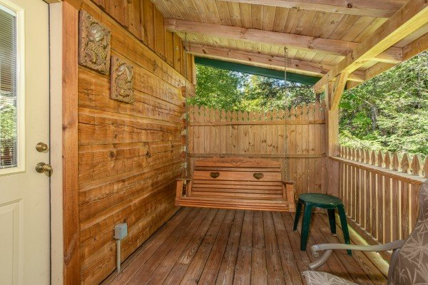 Swing on a covered deck at Forever Yours, a 1-bedroom cabin rental located in Pigeon Forge