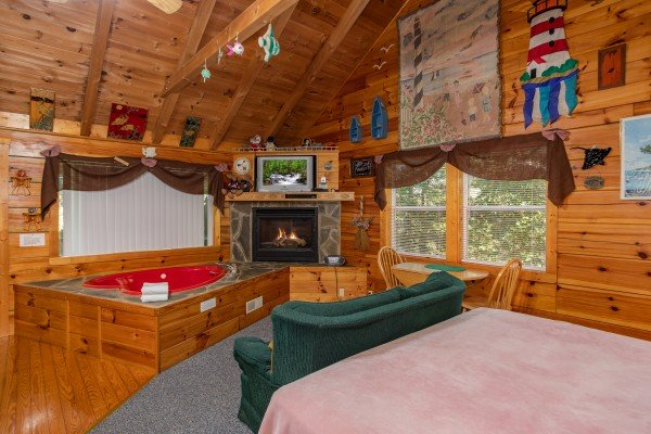 A studio concept living space with bed, loveseat, jacuzzi, fireplace, and TV at Forever Yours, a 1-bedroom cabin rental located in Pigeon Forge