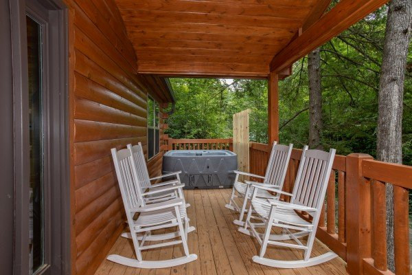 Covered porch with rocking chairs and a hot tub at Paws on the Porch, a 2 bedroom cabin rental located in Gatlinburg